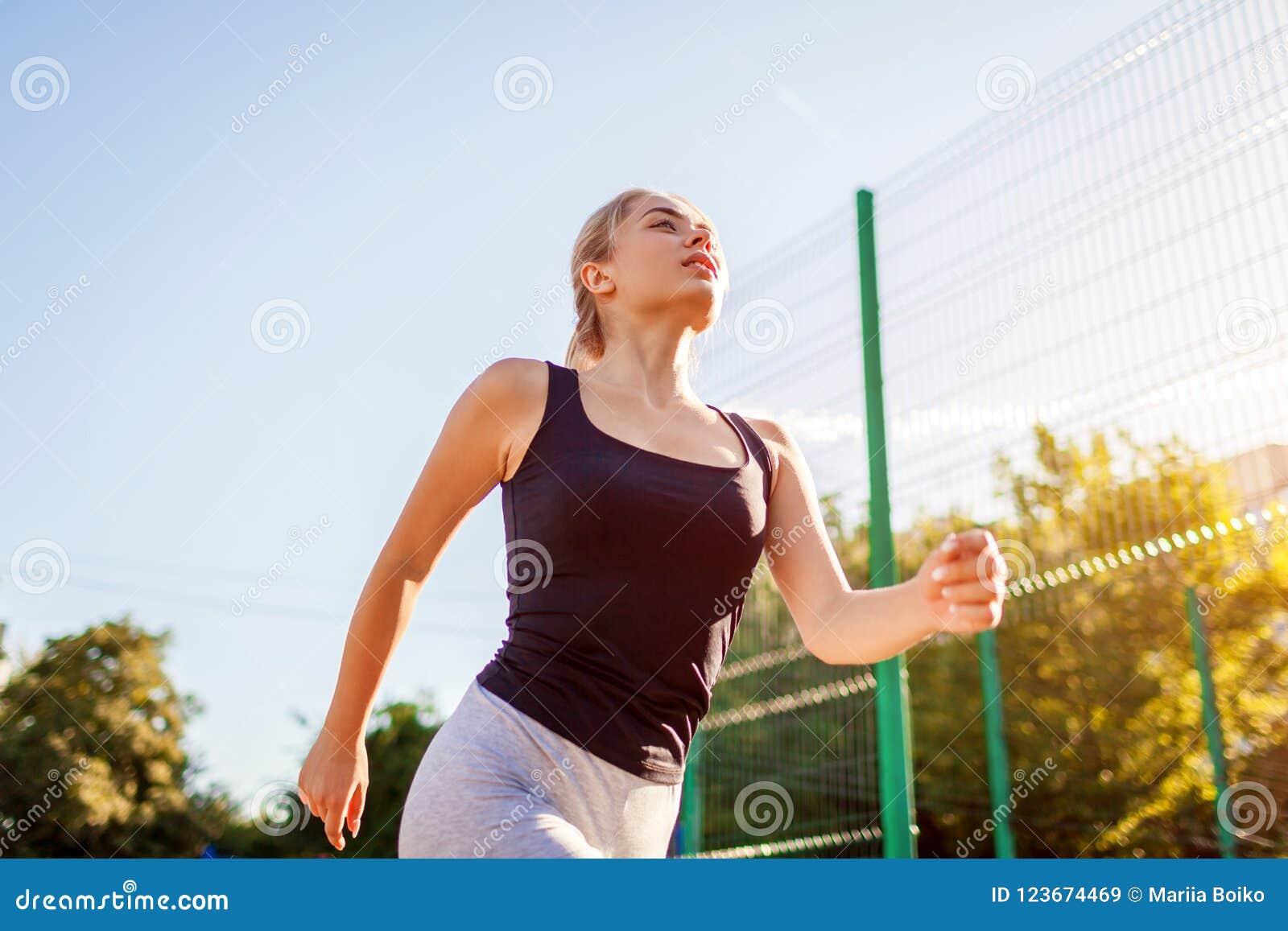 Jonge vrouwenatleet die op sportsground in de zomer lopen Gezonde manier van het leven