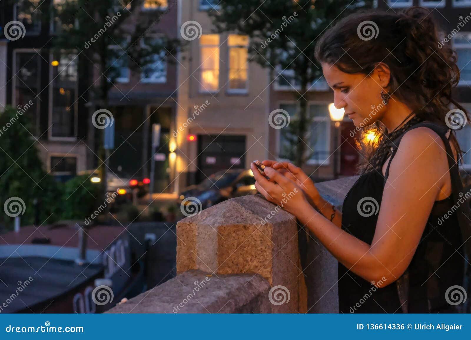 Jonge vrouwenfotograaf met smartphone op een brug