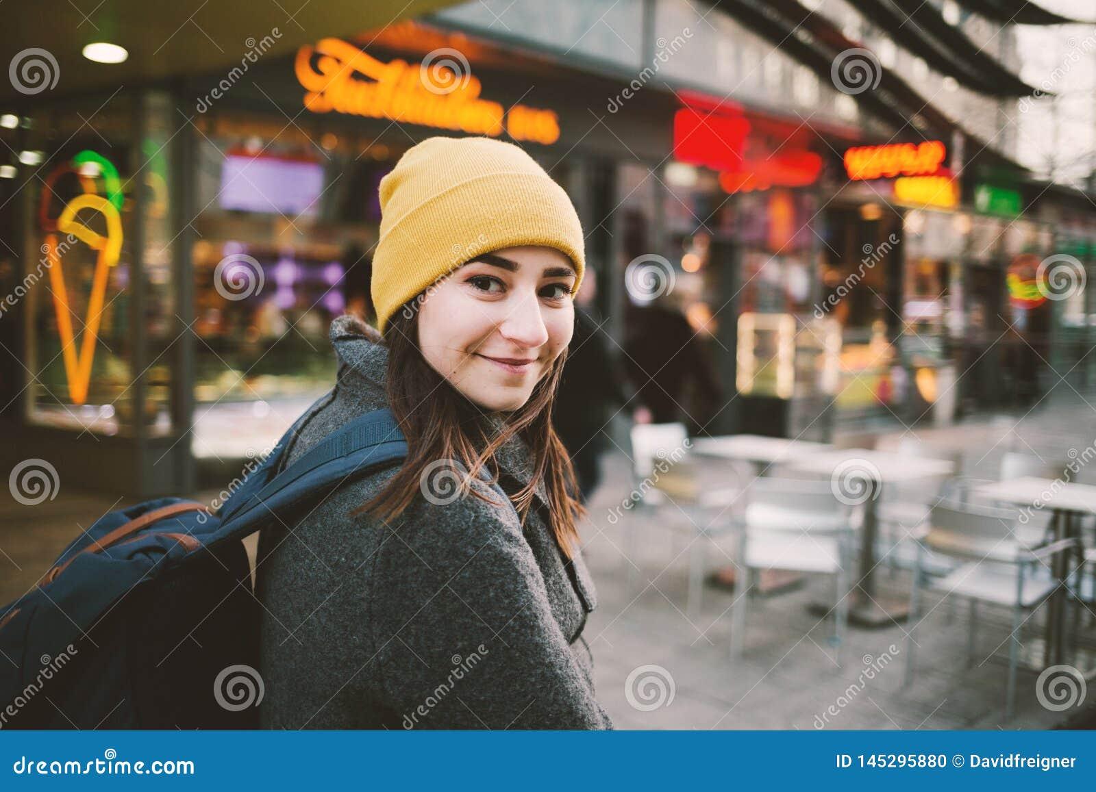 Jonge vrouwengangen door een straat met neontekens Reis, levensstijl en de jeugdconcept