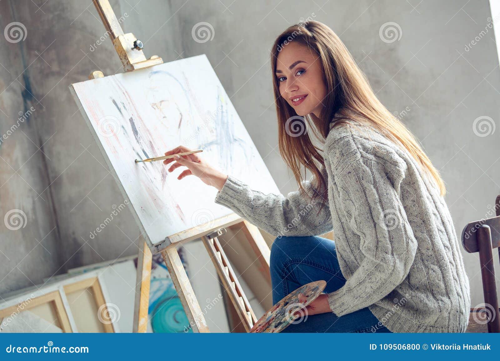 Jonge vrouwenkunstenaar die thuis creatief het schilderen beeld schilderen