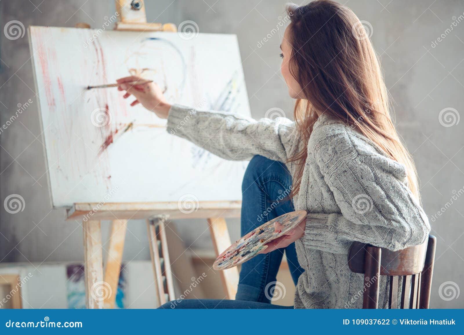 Jonge vrouwenkunstenaar die thuis creatief portret in proces schilderen