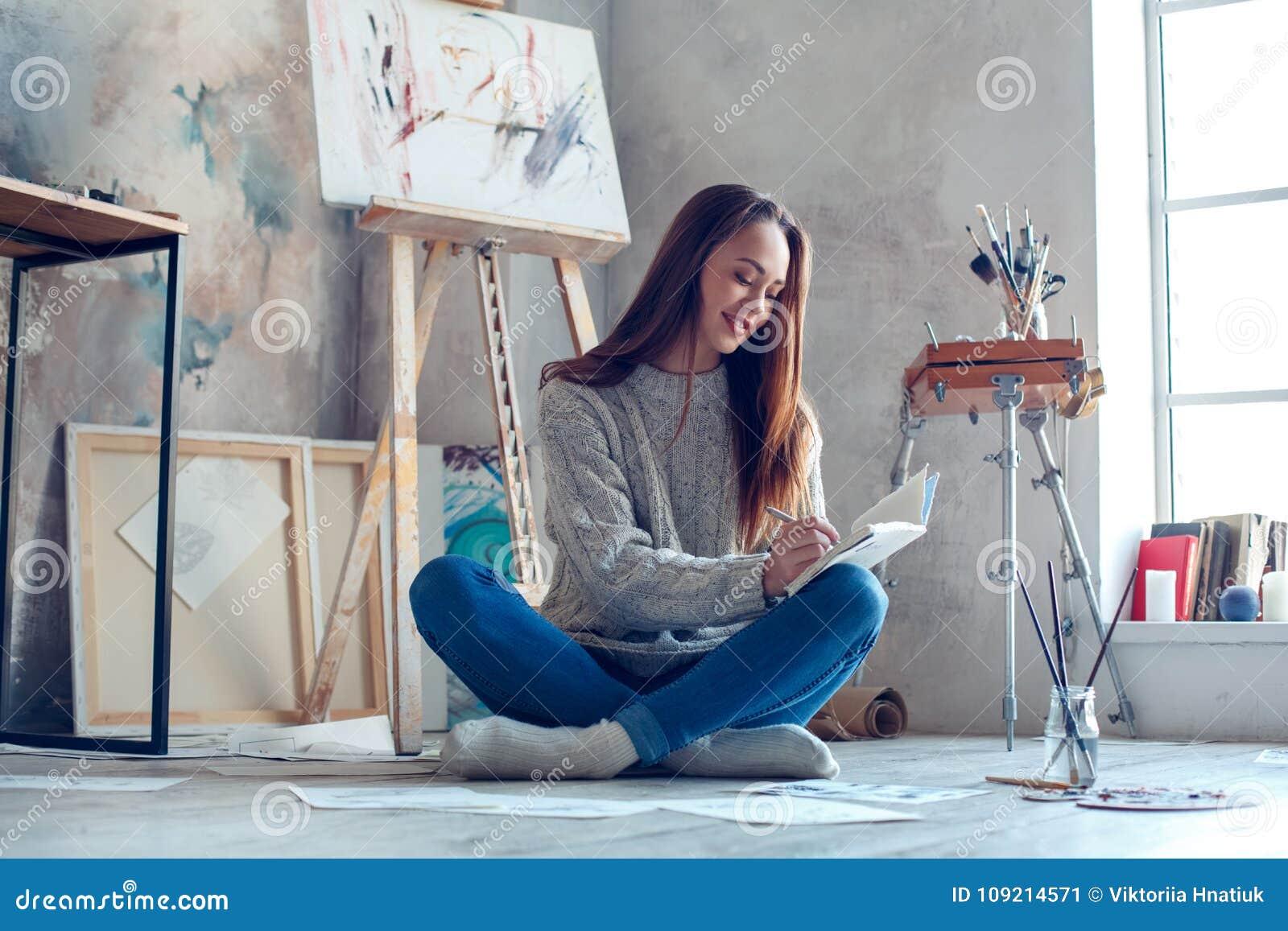 Jonge vrouwenkunstenaar die thuis creatieve planning schilderen