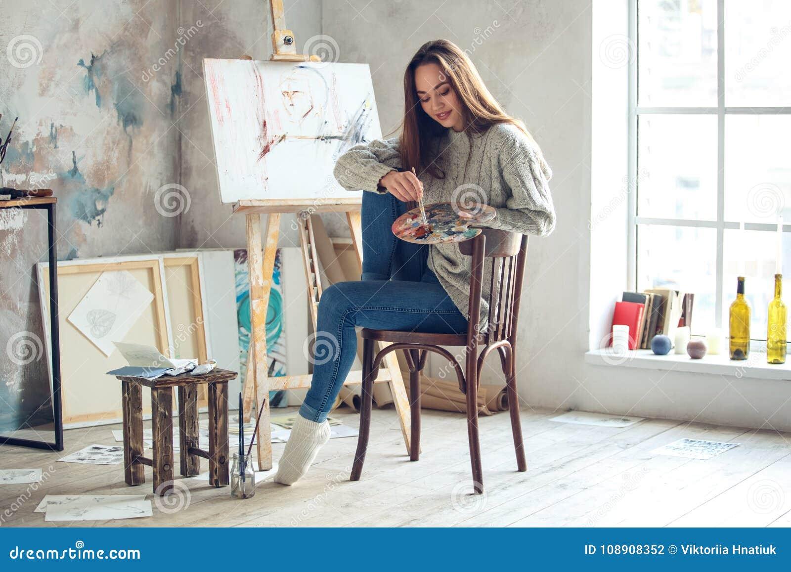 Jonge vrouwenkunstenaar die thuis het creatieve kijken onderaan het glimlachen schilderen
