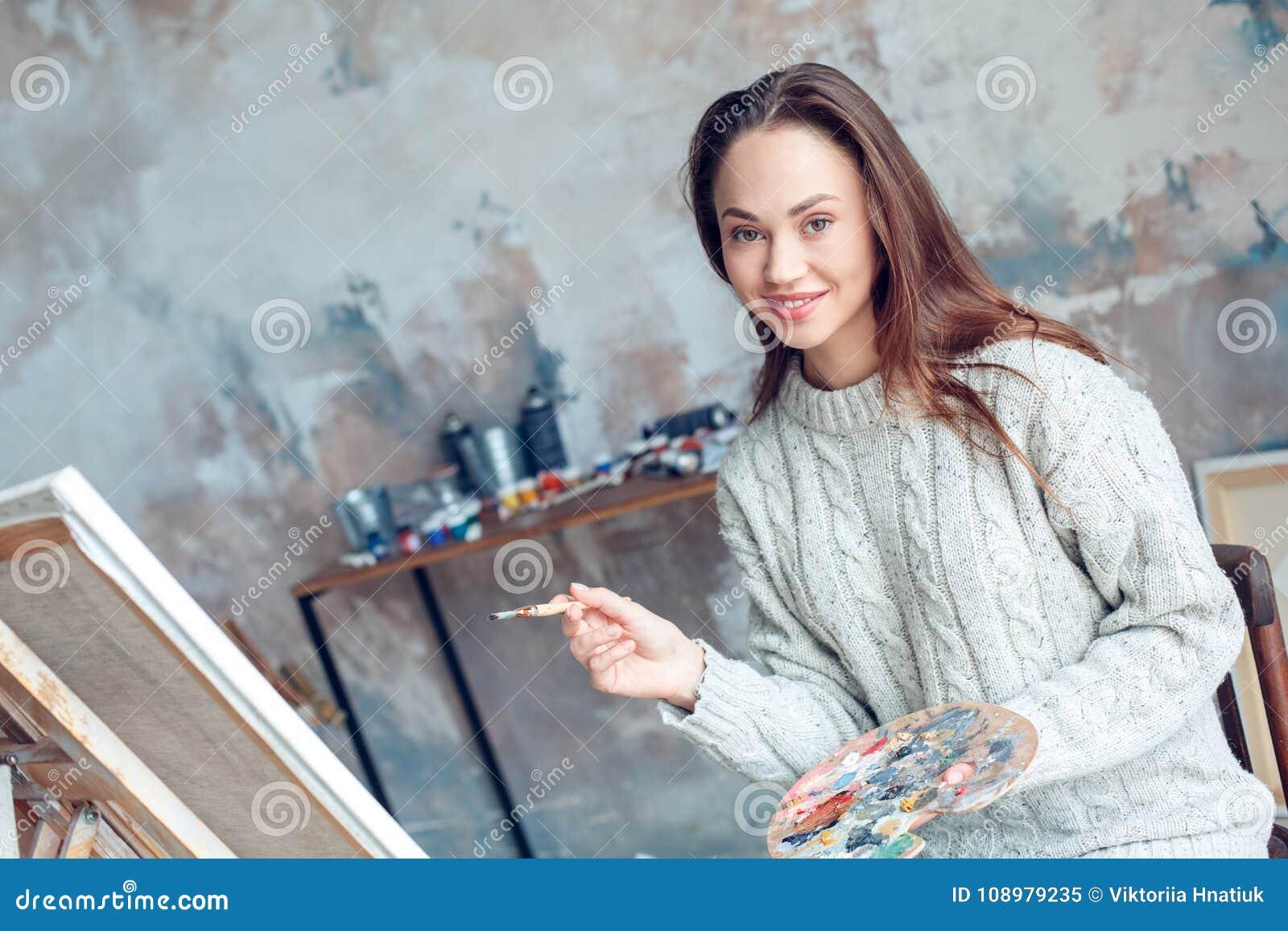 Jonge vrouwenkunstenaar die thuis het creatieve tekening glimlachen schilderen
