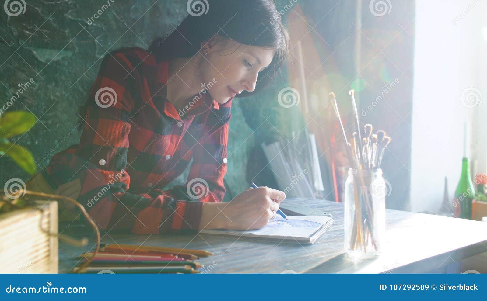 Jonge vrouwenkunstenaar het schilderen schets op document notitieboekje met potlood Heldere zongloed van venster