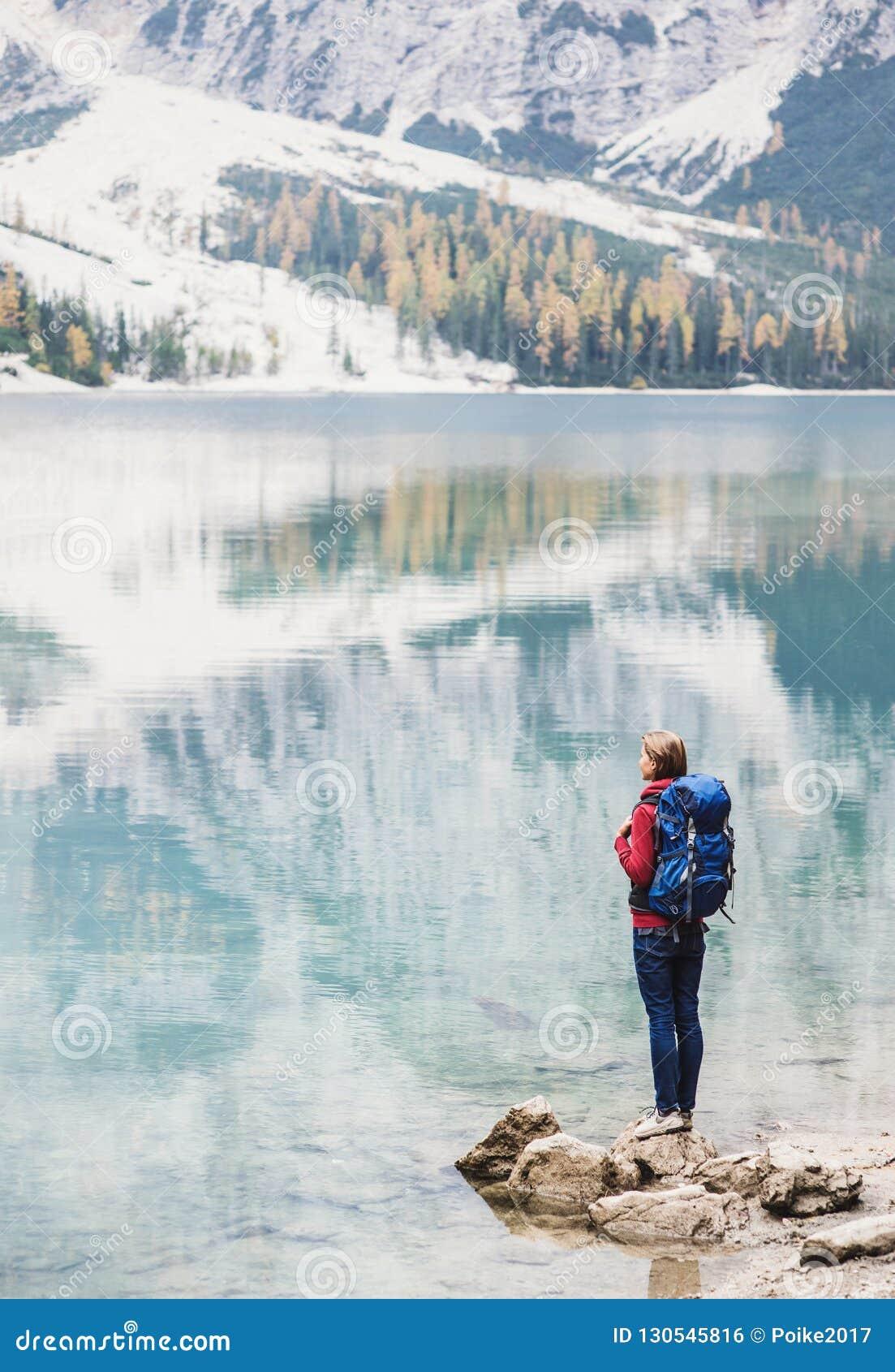 Jonge vrouwenreiziger die in de bergen van Alpen op een meer kijken Reis, de winter en actief levensstijlconcept