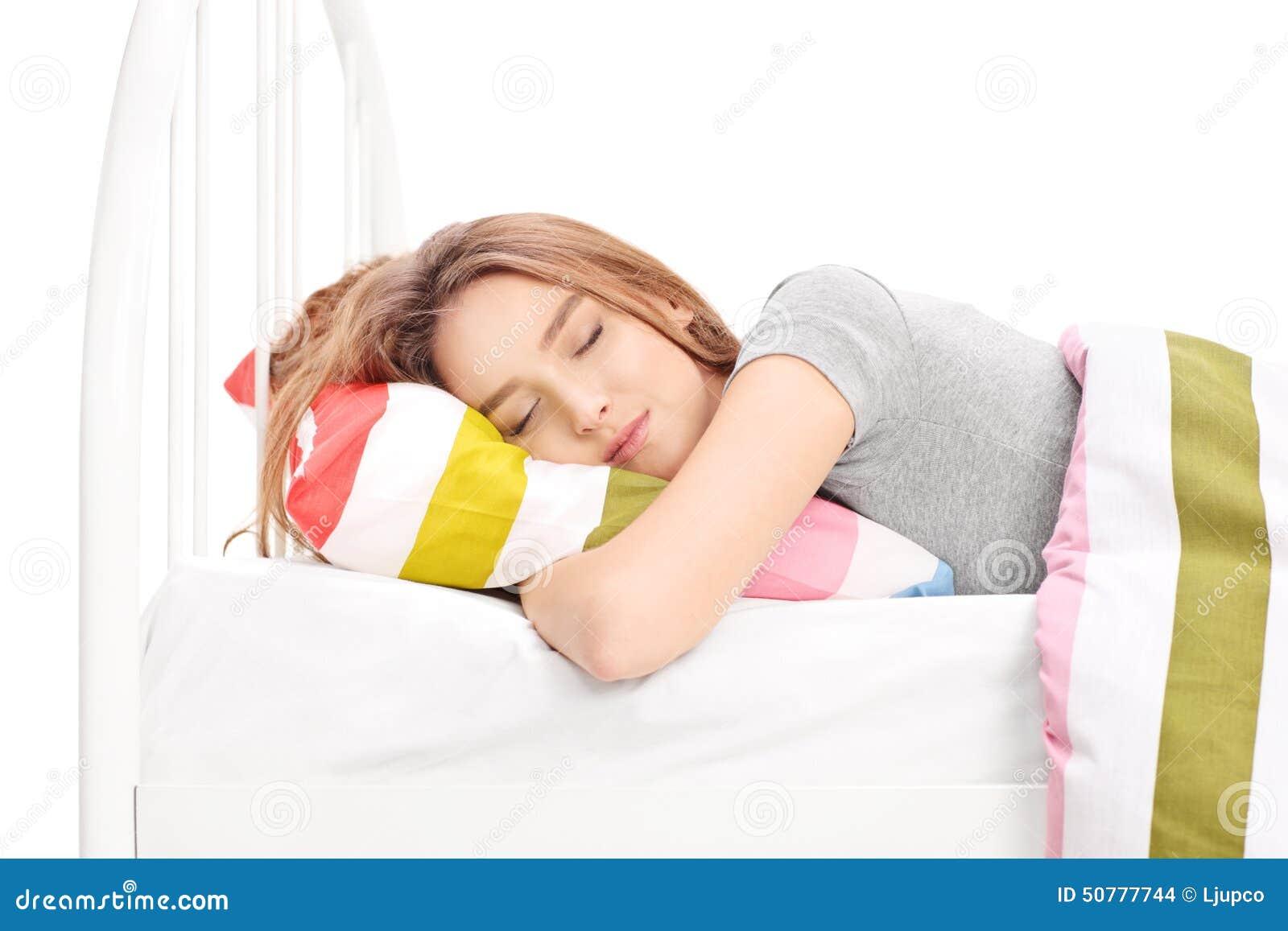 Jonge vrouwenslaap in een comfortabel bed