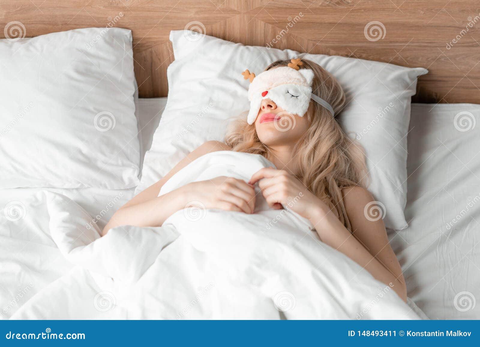 Jonge vrouwenslaap op comfortabel bed in een masker voor slaap Blinddoek op oog Ochtend in hotelruimte Wit hoofdkussen en