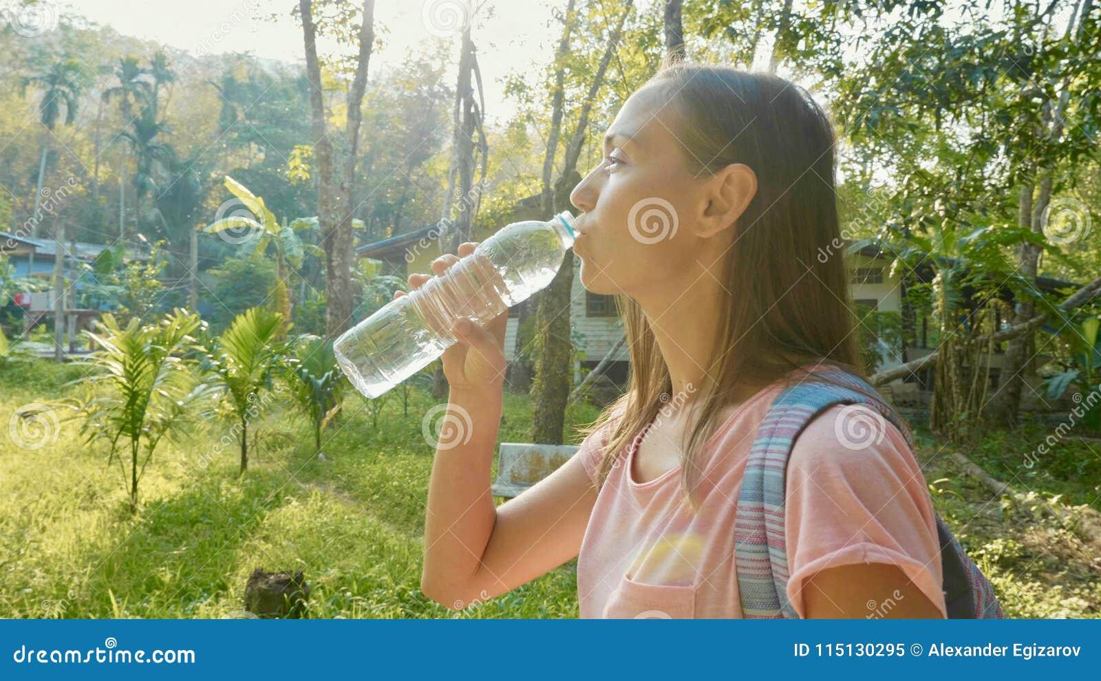 Jonge vrouwentribune op plattelandsweg in Aziatisch dorp en drinkwater