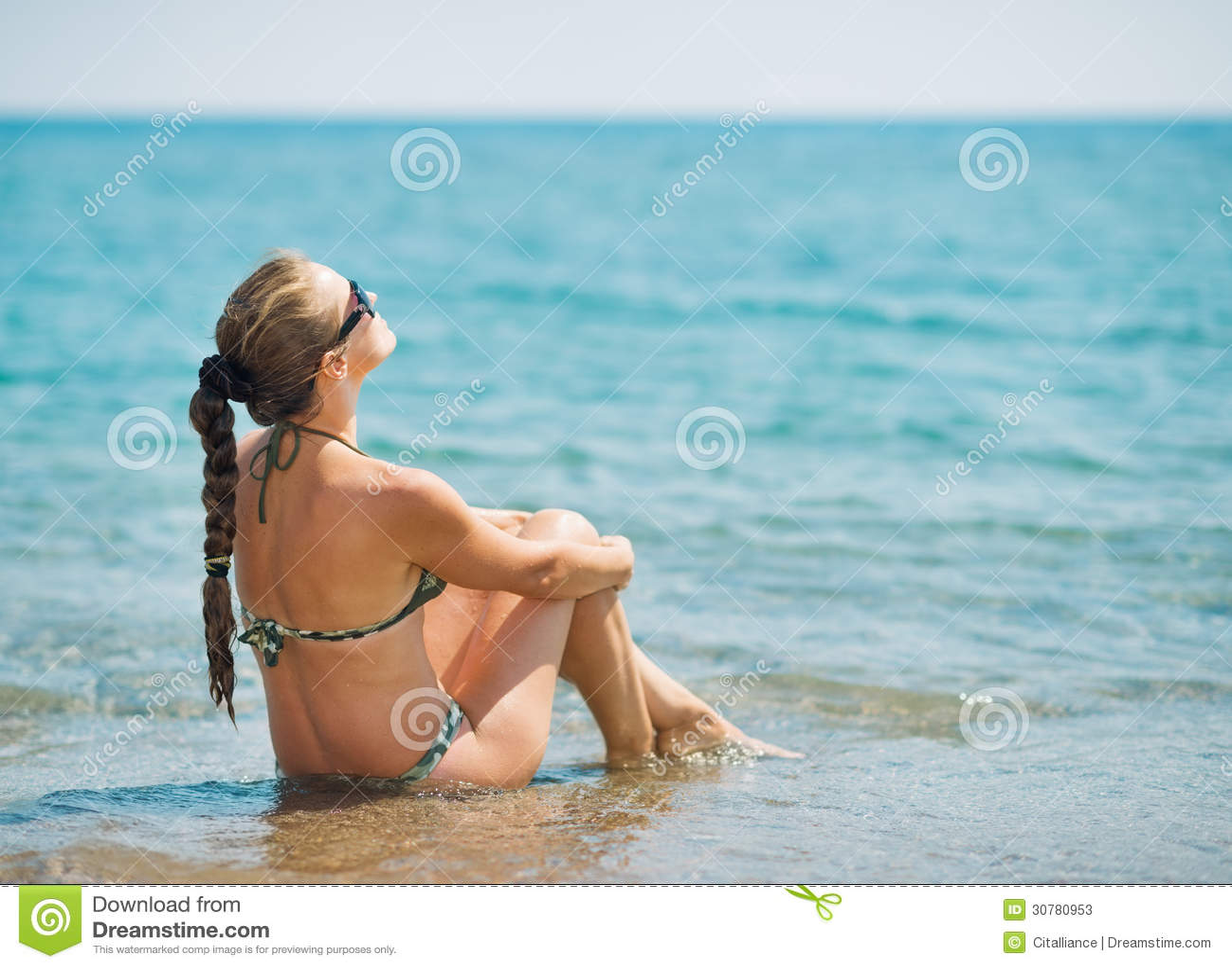 Jonge vrouwenzitting bij kust.