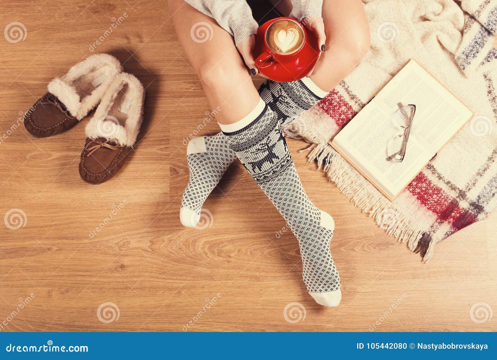 Jonge vrouwenzitting op de houten vloer met kop van koffie, plaid, koekje en boek Close-up van vrouwelijke benen in warme sokken