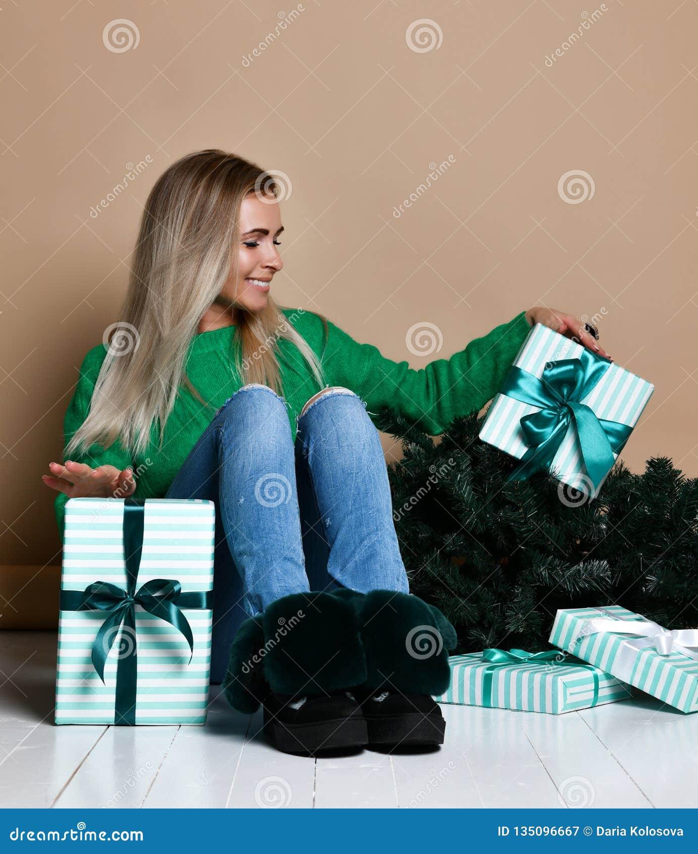 Jonge vrouwenzitting op de vloer dichtbij sparkerstboom en het dromen over huidige, toekomstige, giften en het wachten van een mi
