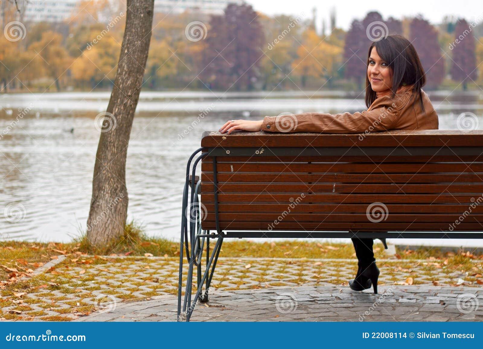 Jonge vrouwenzitting op een bank in het park