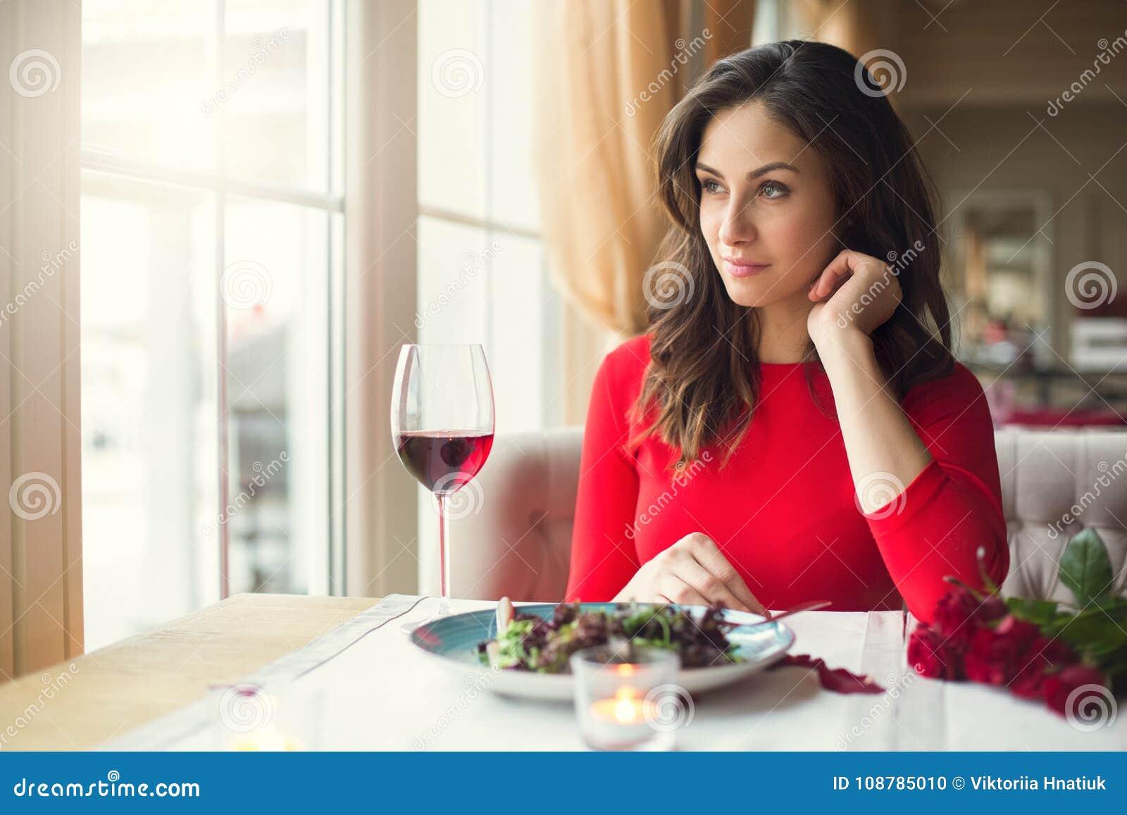 Jonge vrouwenzitting in restaurant dineren die uit het venster kijken