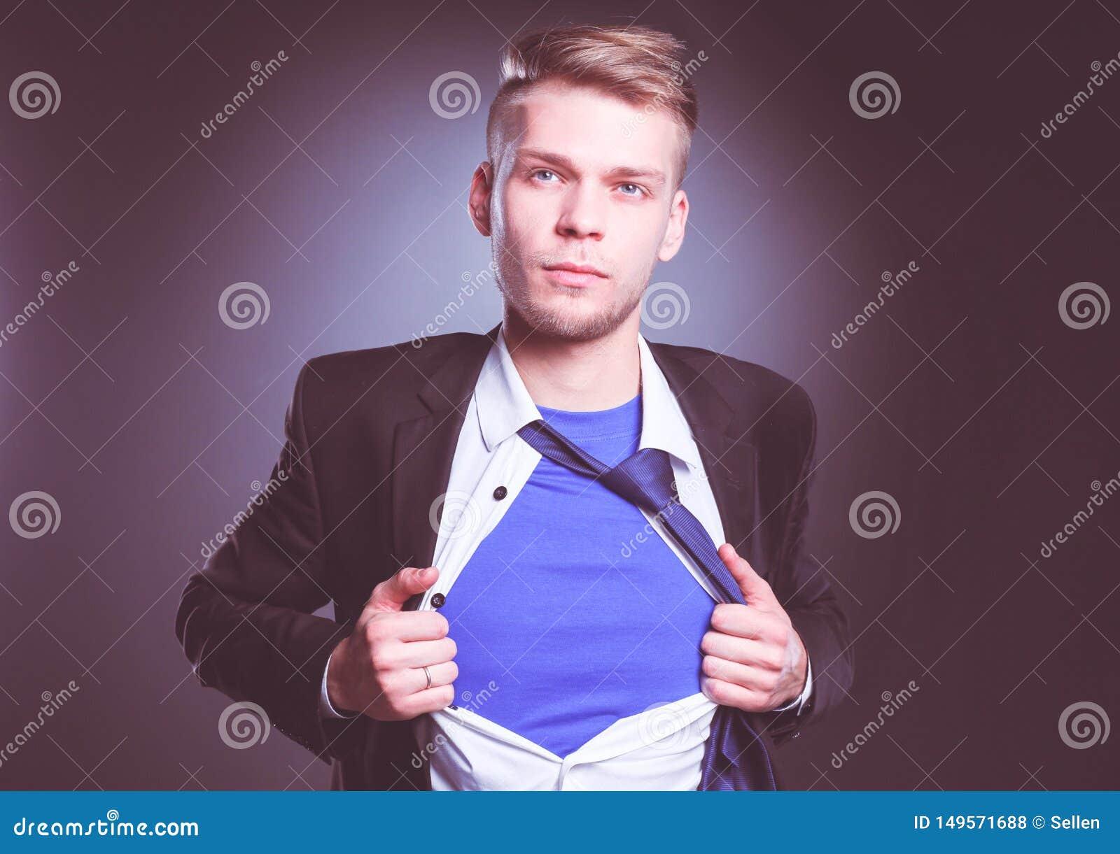 Jonge zakenman die als een super held handelen en tearing zijn ge?soleerd overhemd, op grijze achtergrond Jonge zakenman