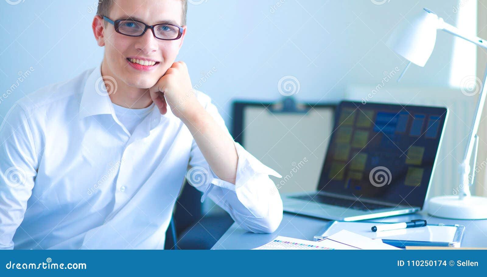 Jonge zakenman die in bureau werkt, dat dichtbij bureau zit