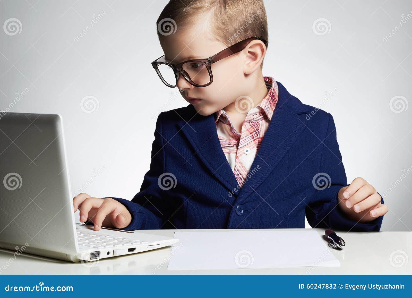 Jonge zakenman die laptop met behulp van Ernstig kind in glazen