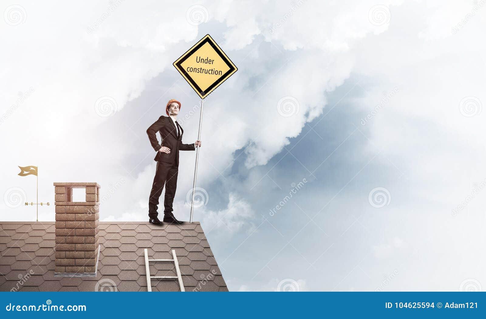 Download Jonge Zakenman Die Op Het Dak Van De Huisbaksteen Geel Uithangbord Houden Stock Foto - Afbeelding bestaande uit bouw, ingenieur: 104625594