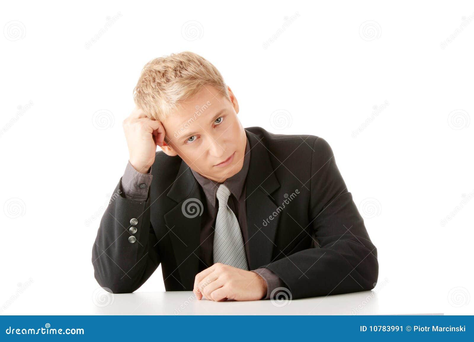 Jonge zakenmanzitting achter het bureau