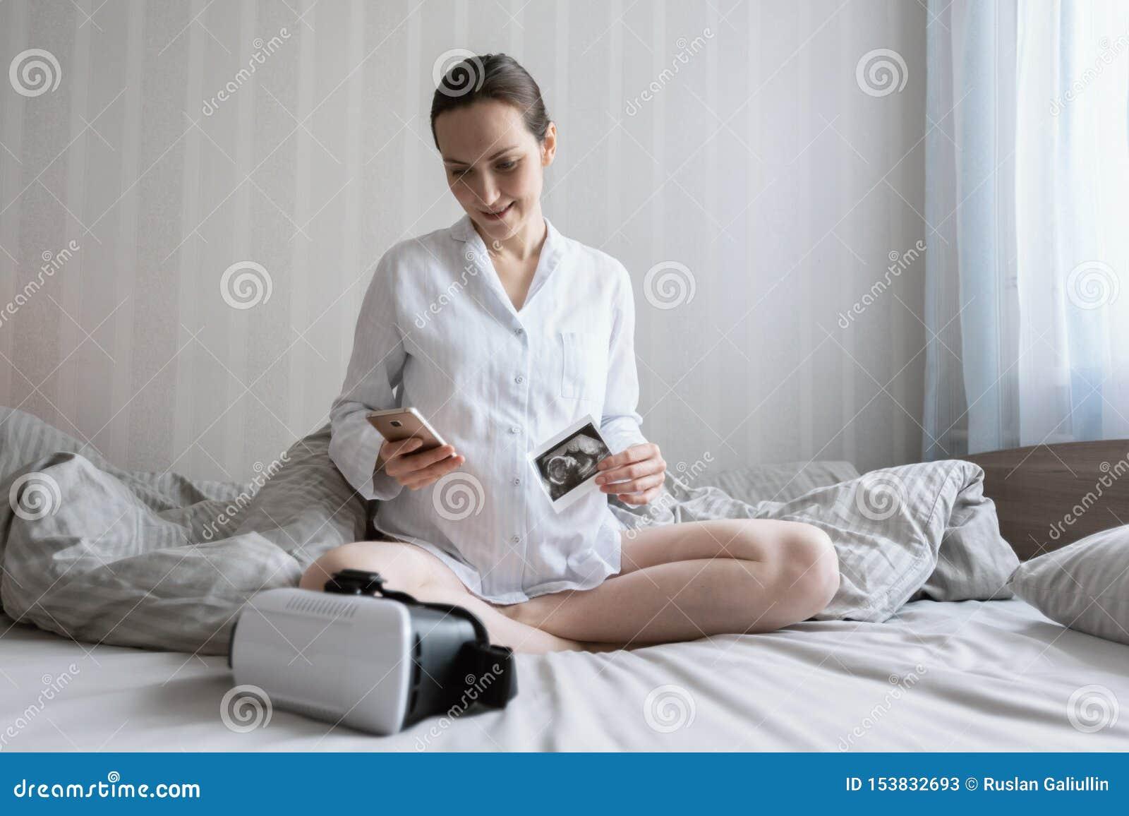 Jonge zwangere Kaukasische vrouwenzitting op bed met smartphone en ultrasone klankbeeld en vr glazen