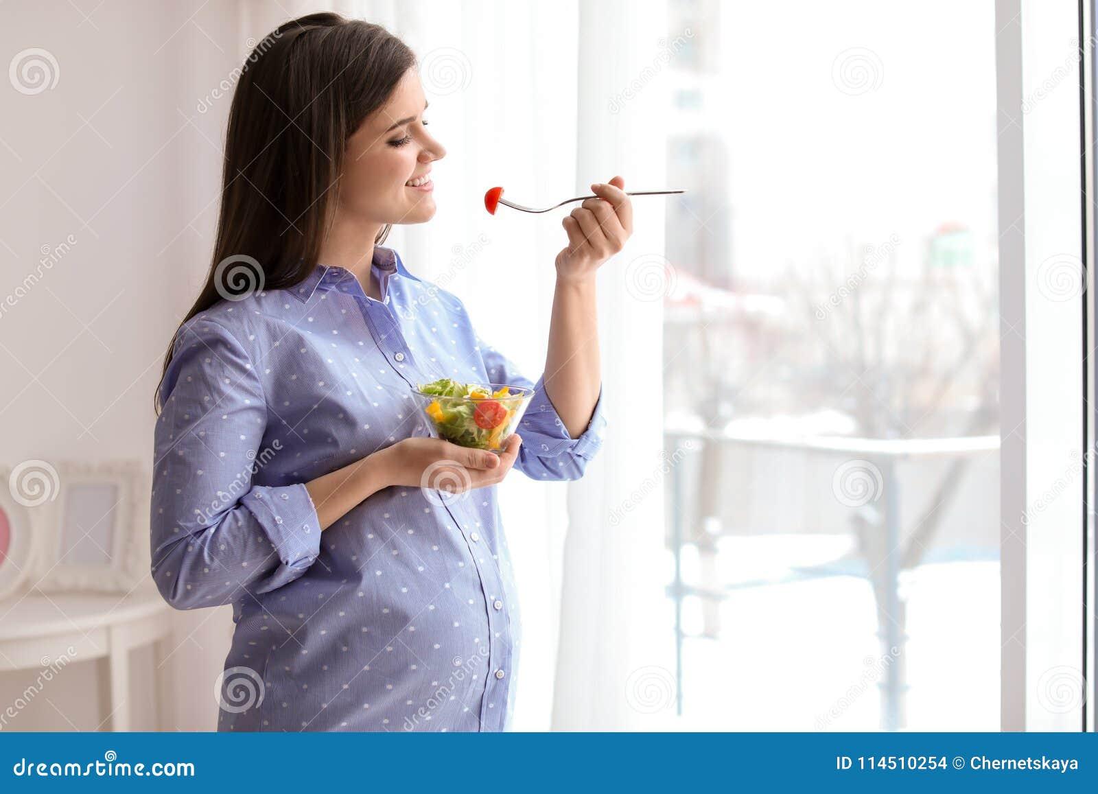 Jonge zwangere vrouw die plantaardige salade eten