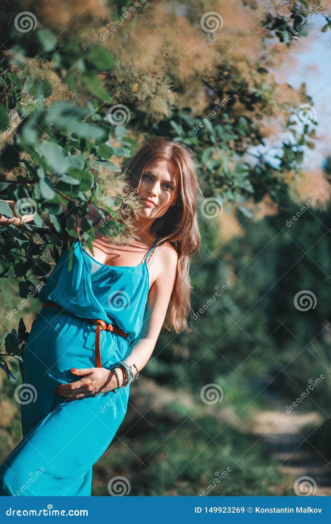 Jonge zwangere vrouw in het park in openlucht Kalme zwangere vrouw in derde trimester Het lopen in openbare tuin