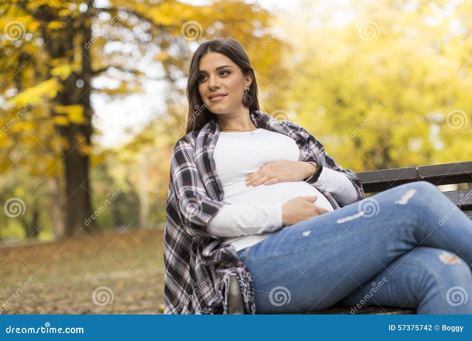 Jonge zwangere vrouwenzitting in het de herfstpark