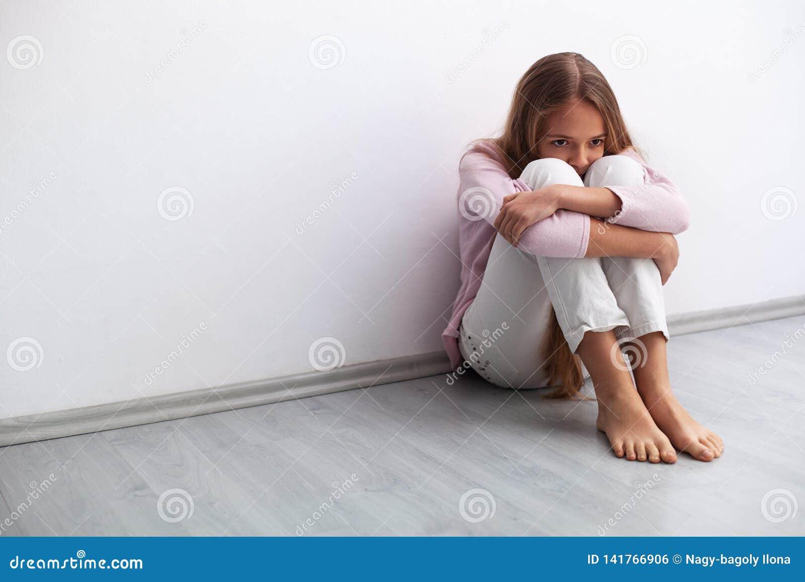 Jongelui of droevige meisjeszitting op de vloer door de muur ongerust die worden gemaakt die