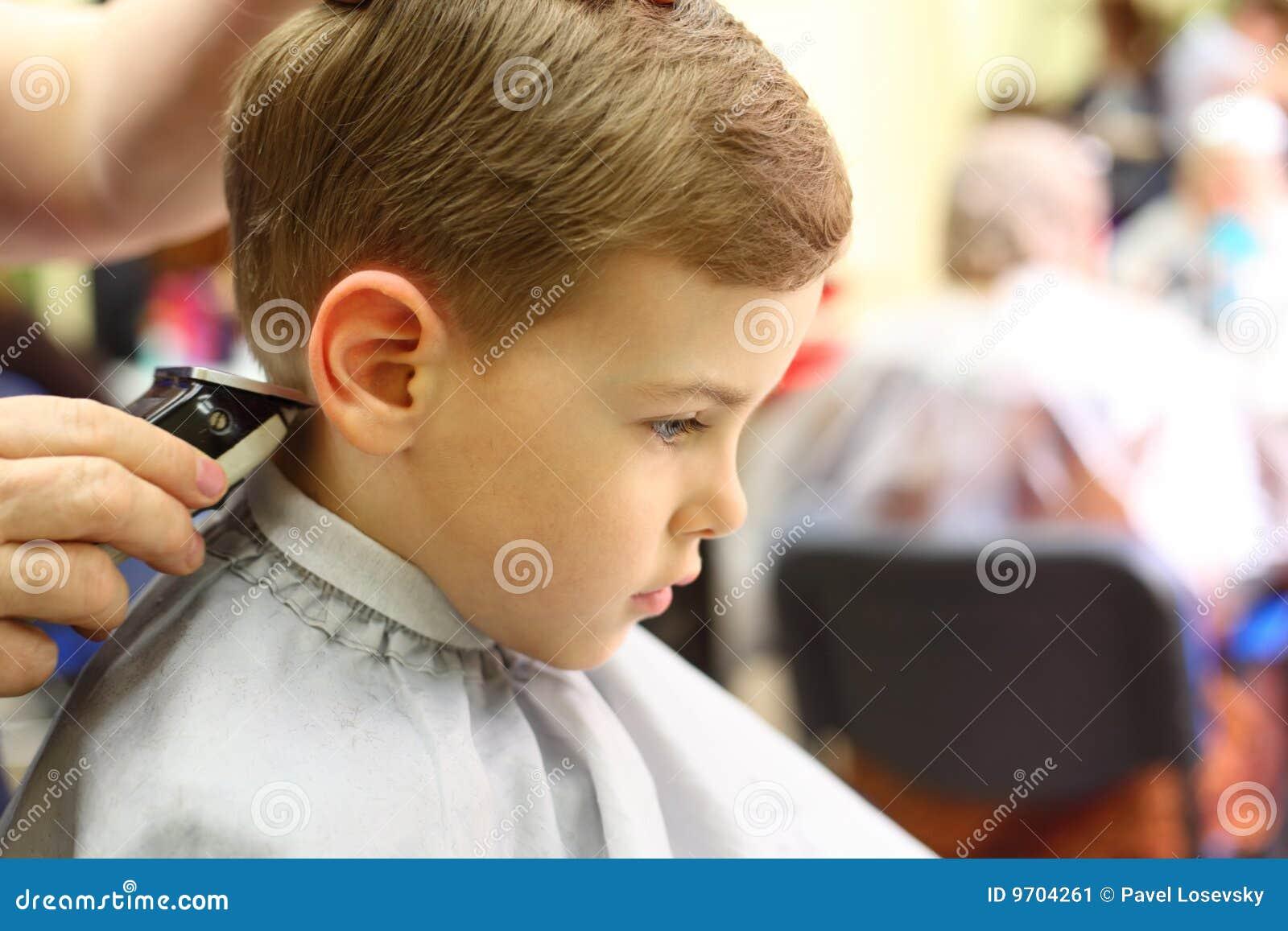 Jongen die in de machine van de kapper wordt gesneden