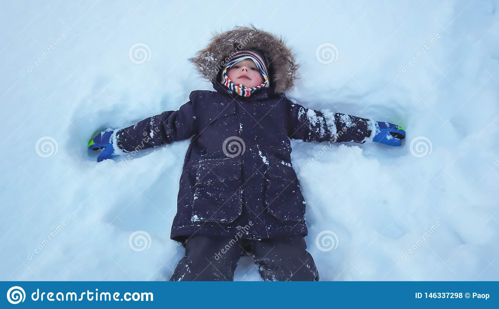 Jongen die in een diepe sneeuw liggen
