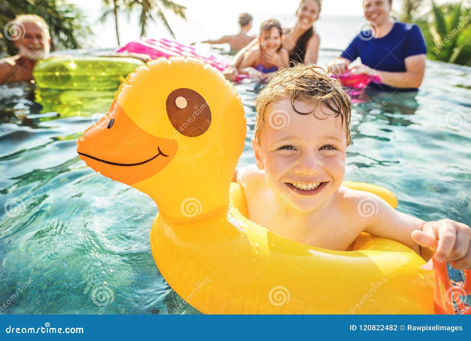 Jongen die in een pool met familie zwemmen