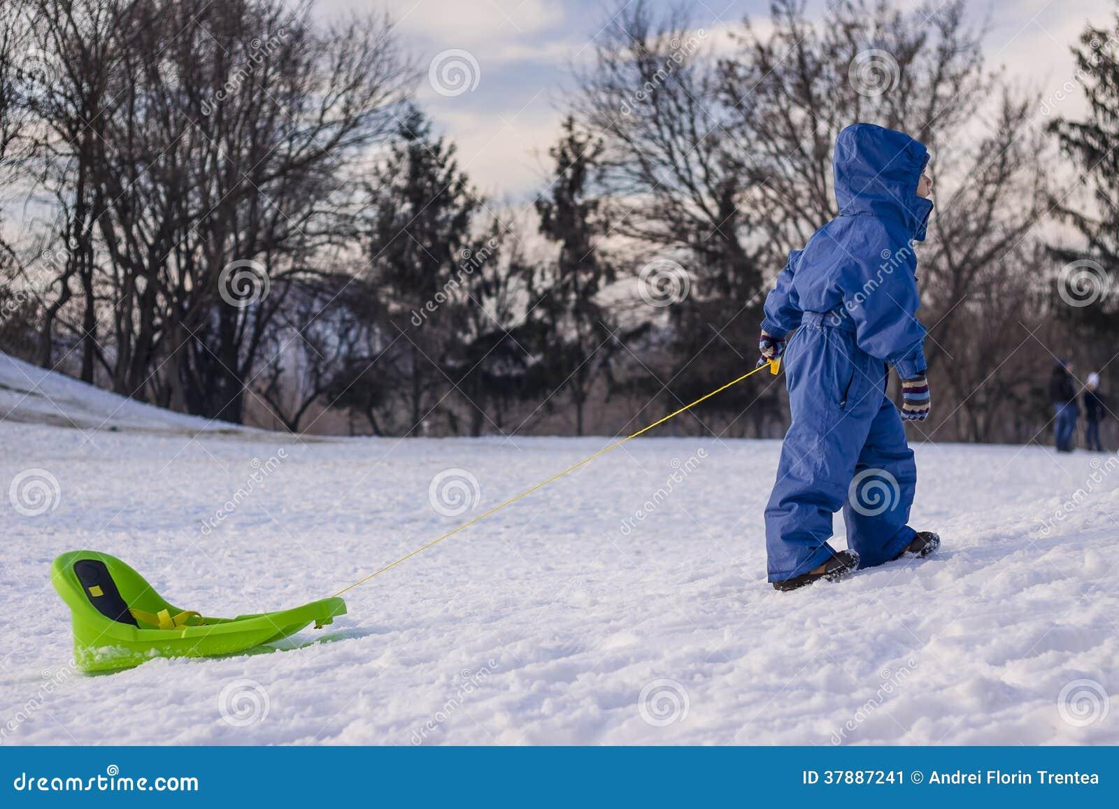 Jongen die een slee op sneeuw trekken