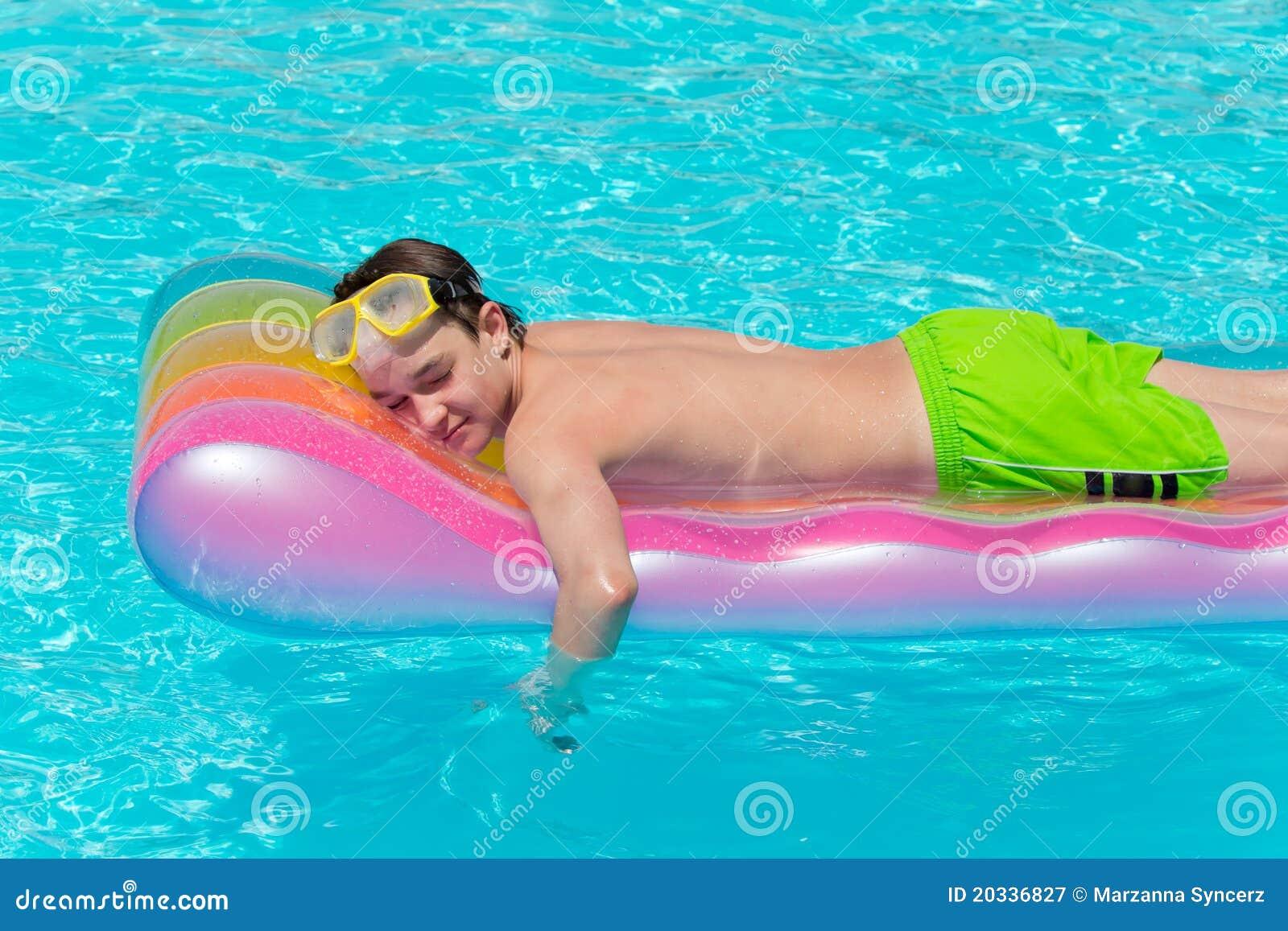 Jongen die op lilo in pool rust
