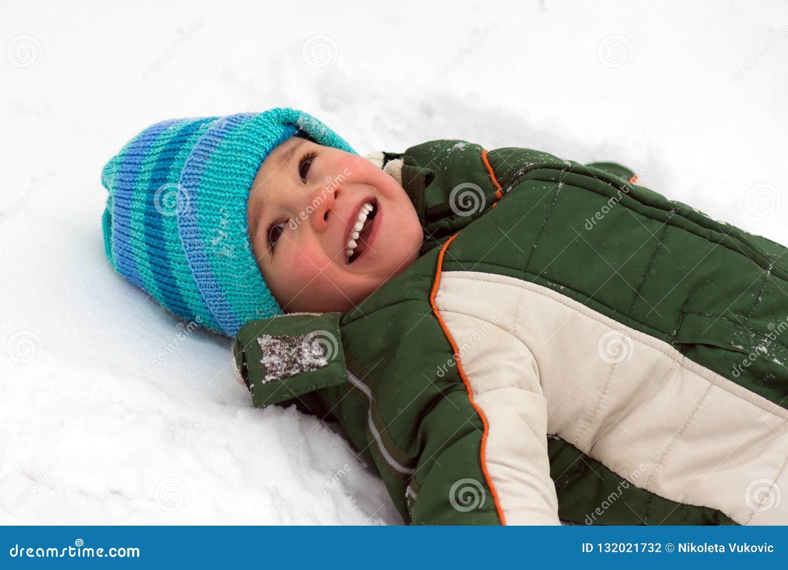 Jongen die op sneeuw liggen