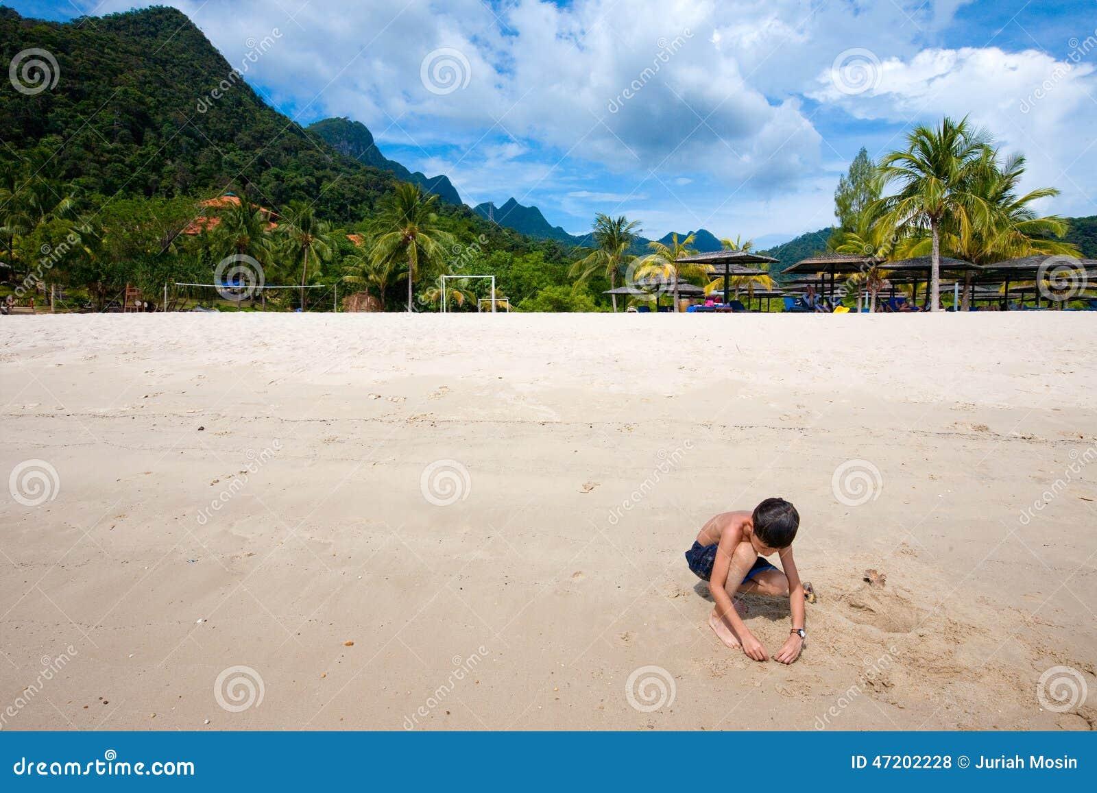 Jongen die pret hebben die in openlucht in het zand door het strand in tropisch eiland spelen