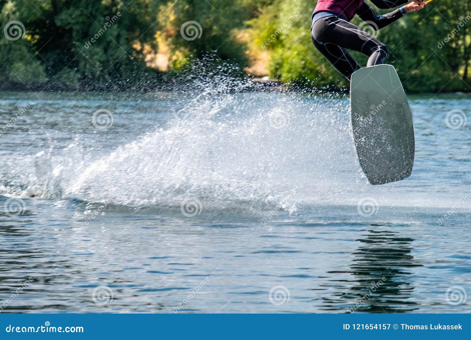 Jongen die pret met waterski op het meer hebben