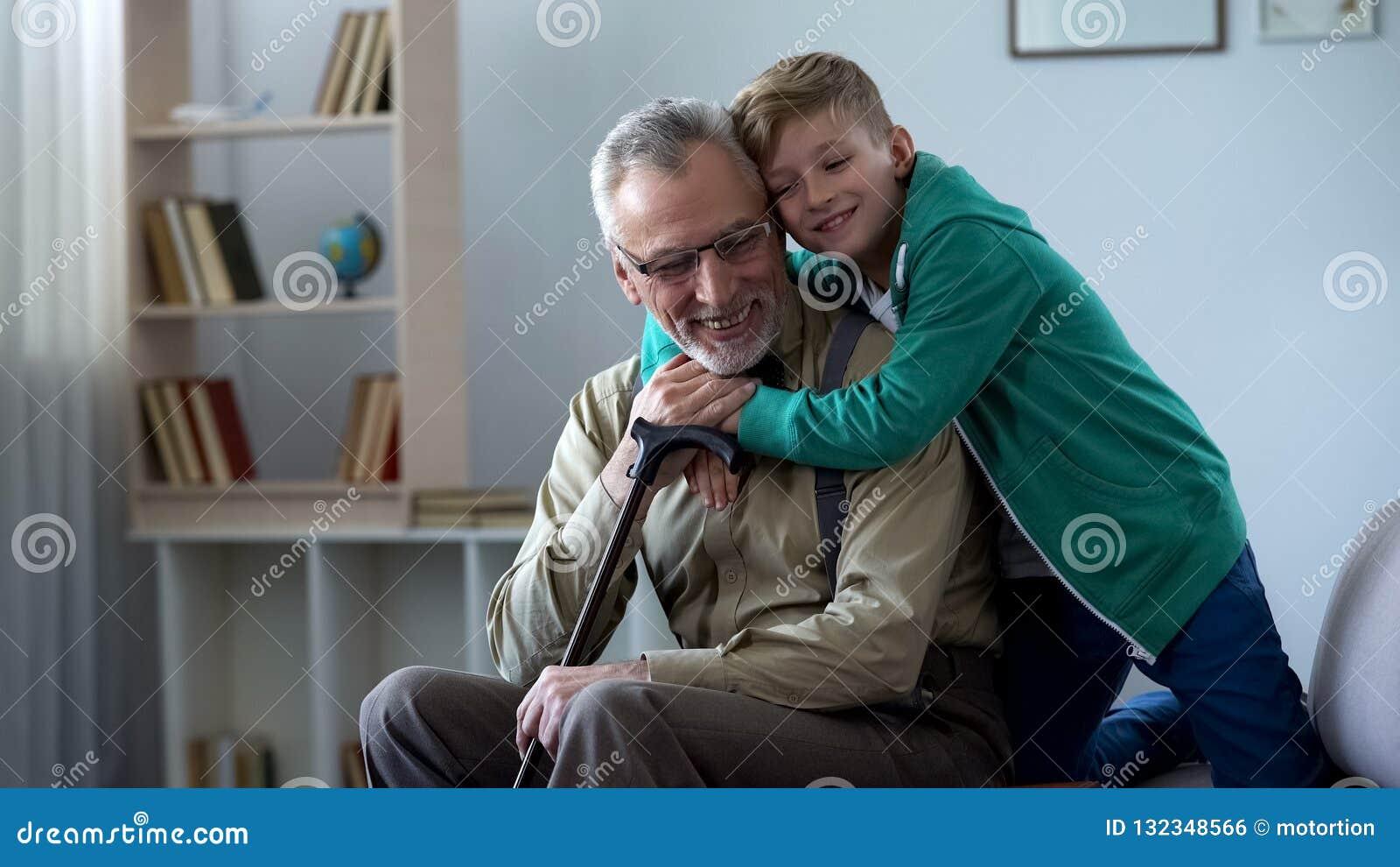 Jongen die teder grootvader, familieliefde, eerbied omhelzen voor oudere generatie