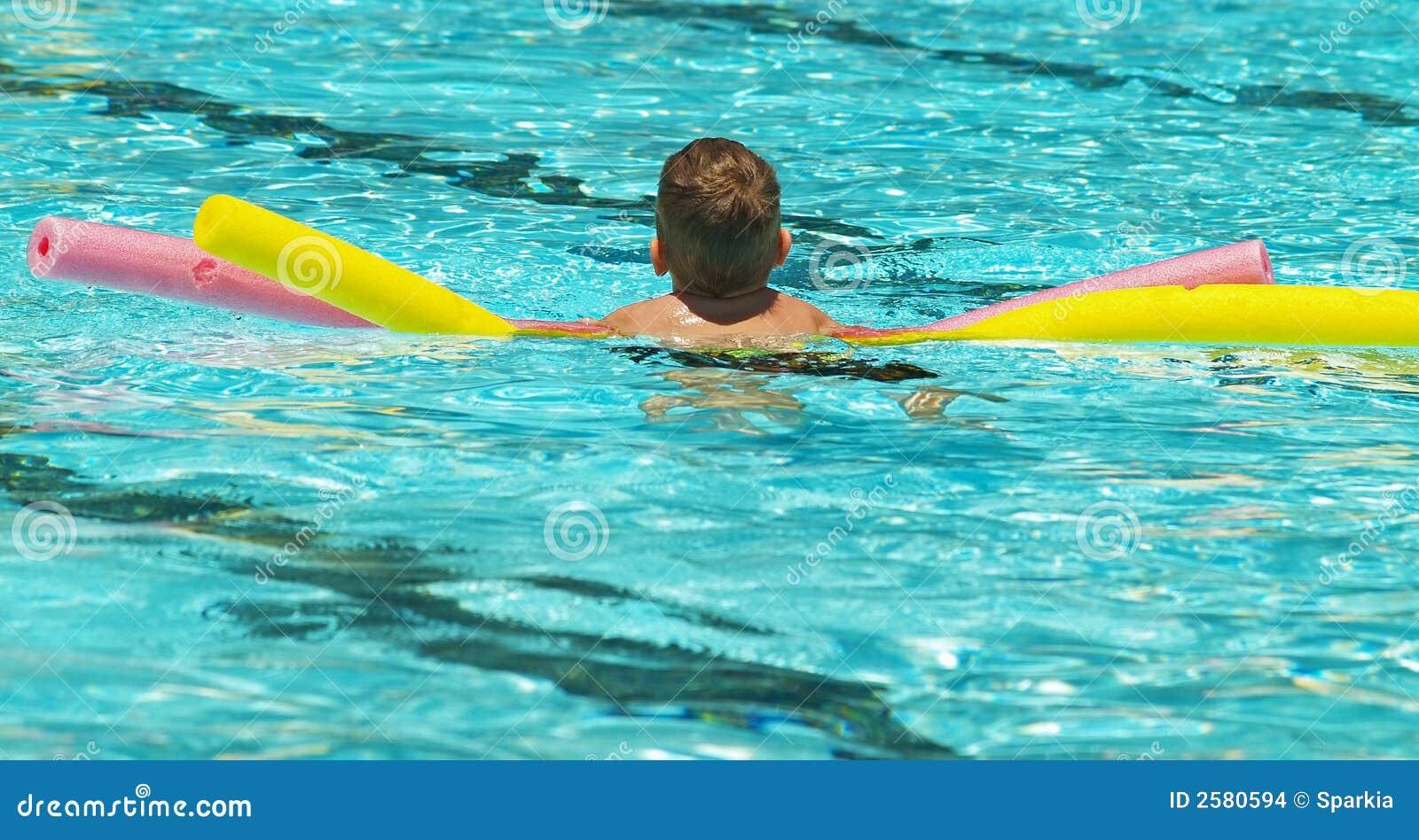 Jongen die vlotters in pool gebruikt