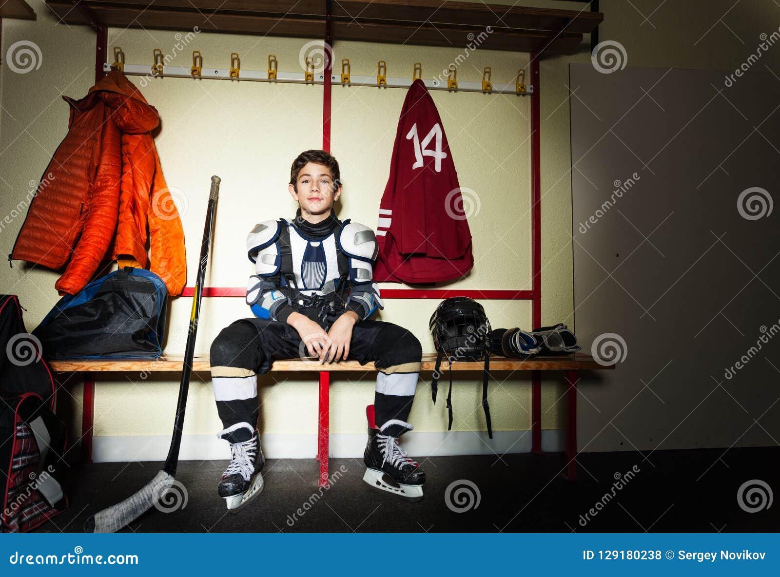 Jongen die voor ijshockeyspel voorbereidingen treffen in kleedkamer