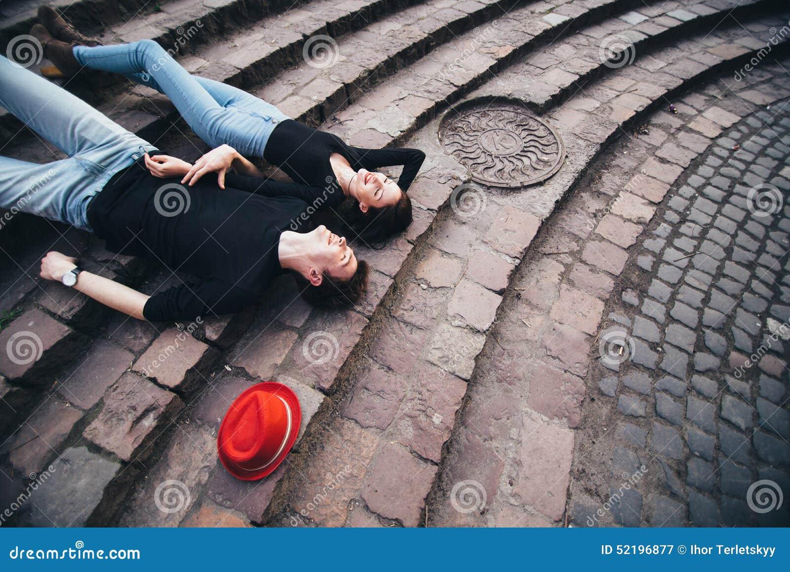 Jongen en meisje die op de treden en de rust liggen
