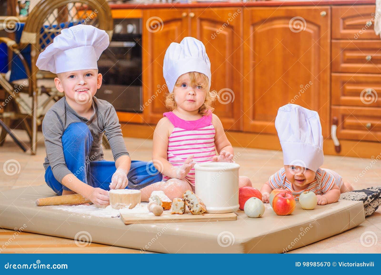 Jongen en meisje en een pasgeboren jong geitje met hen in chef-kok` s hoeden die op de keukenvloer zitten die met bloem wordt bev