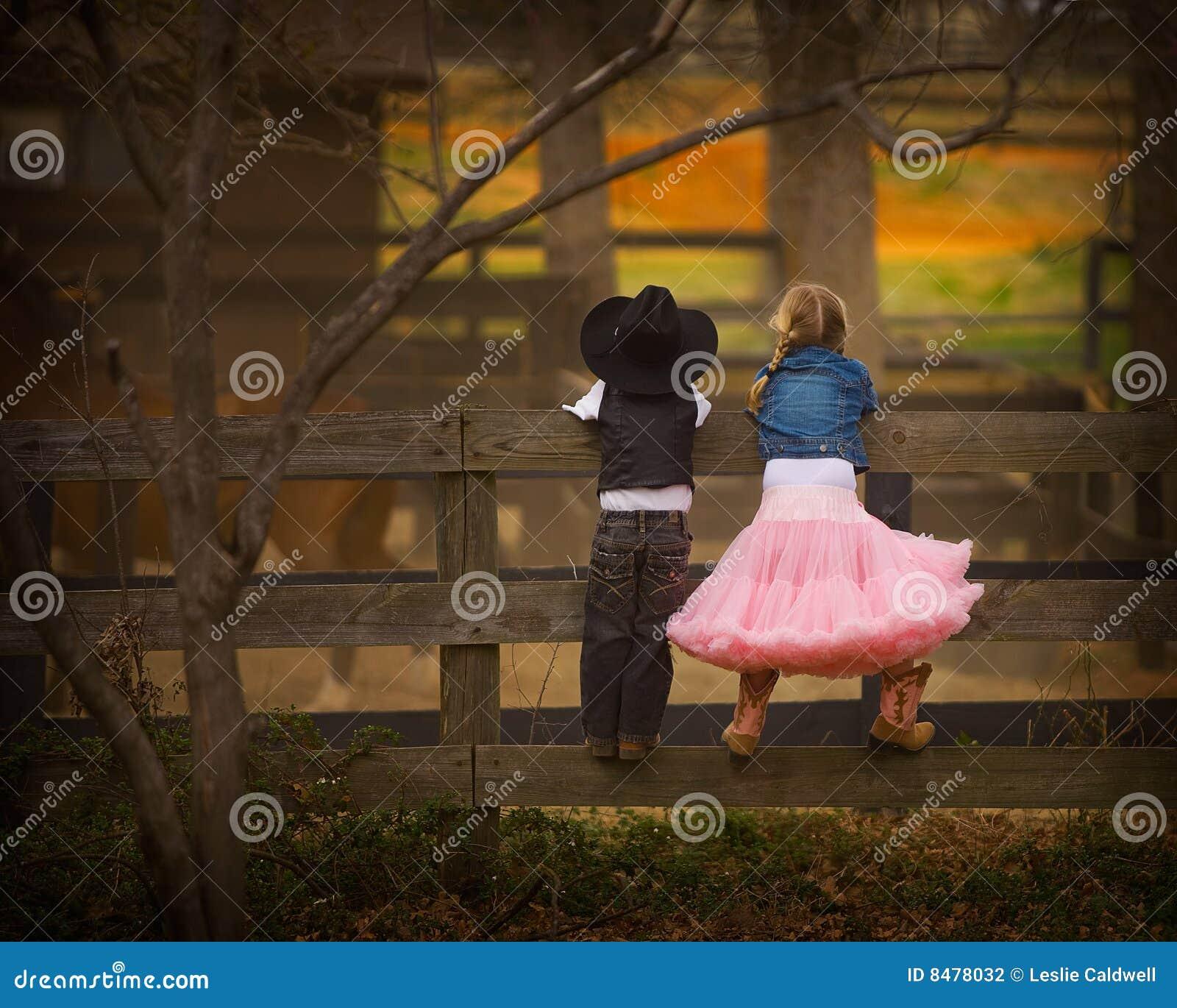 Jongen en meisje op omheining