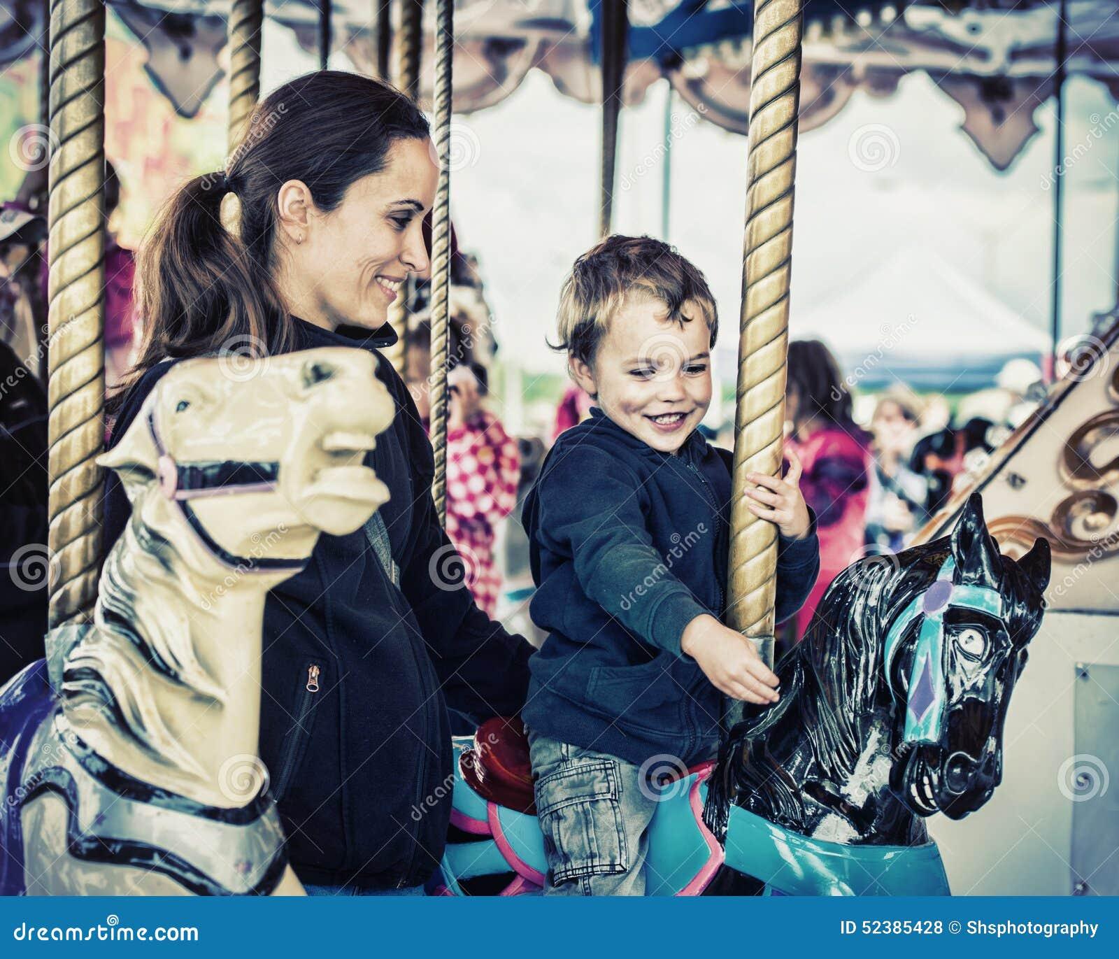 Jongen en Moeder samen op een Retro Carrouselrit -