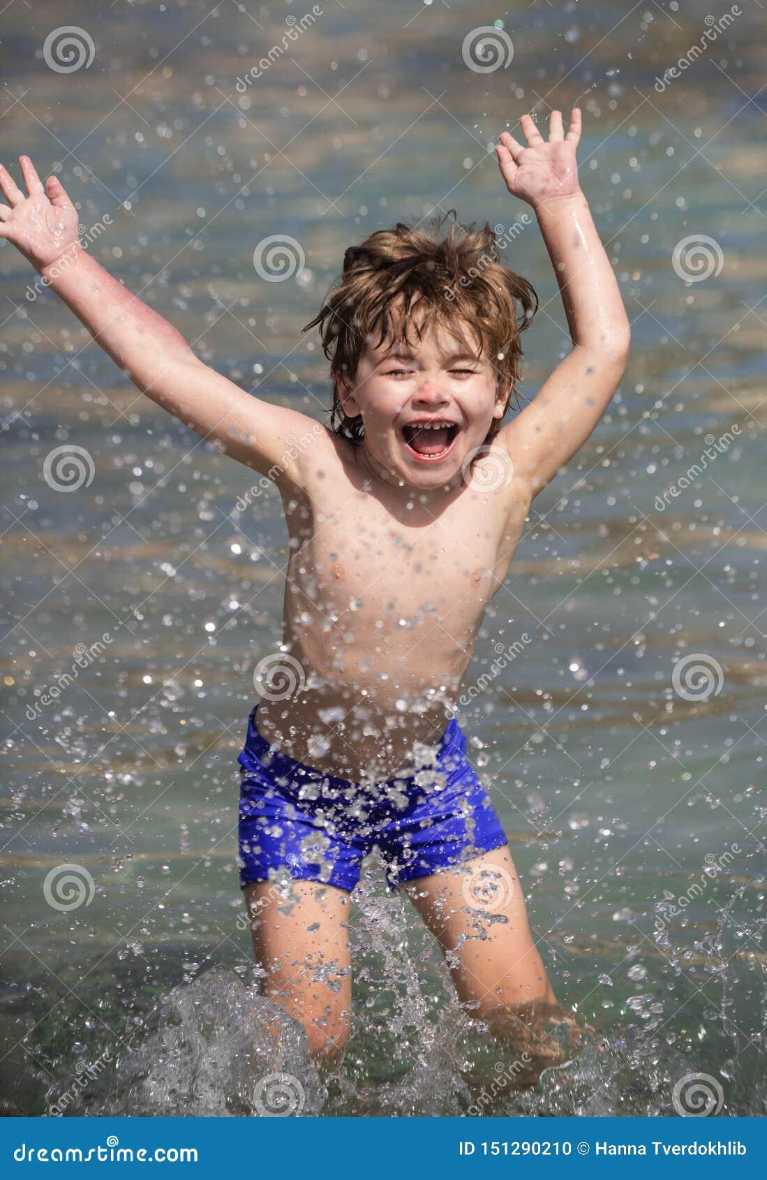 Jongen en waterdalingen Gelukkig kind op zee De zomer Overzeese vakantie Vakantie Het jonge geitje speelt in het water Pret grapp