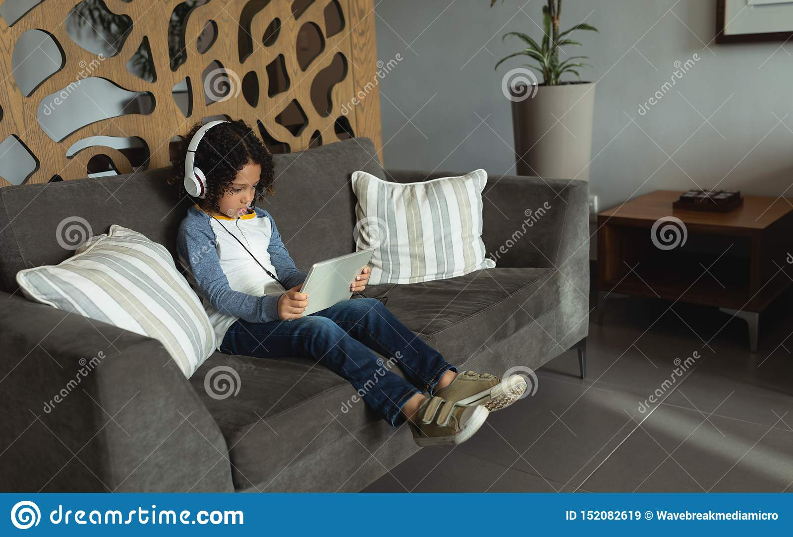 Jongen het luisteren muziek op digitale tablet in de hal bij het ziekenhuis