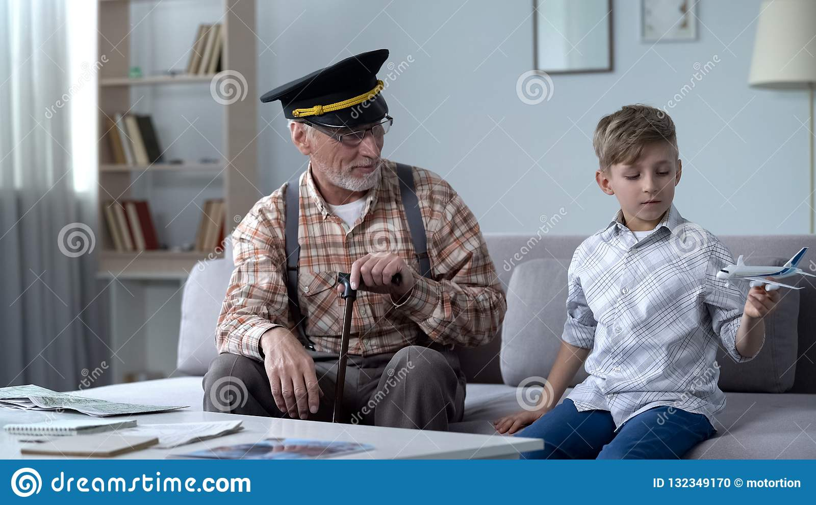 Jongen het spelen met stuk speelgoed vliegtuig, opa vroegere proef trots van kleinzoon, droombaan
