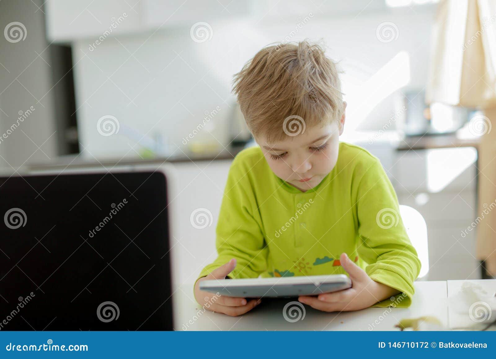 Jongen het spelen op elektronische gadgettablet in zijn slaapkamer Sociaal probleem van mededeling van kinderen in de moderne wer