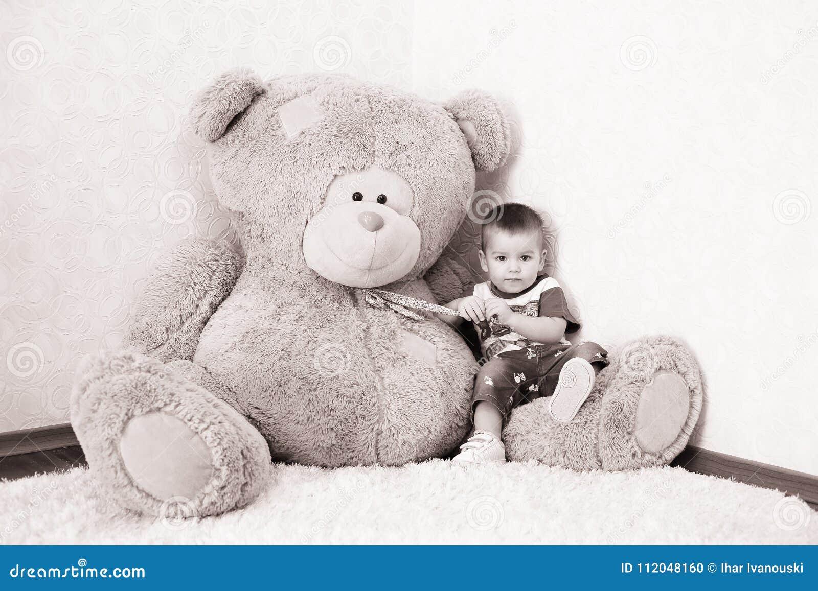 Jongen het stellen dichtbij een groot Teddybeer