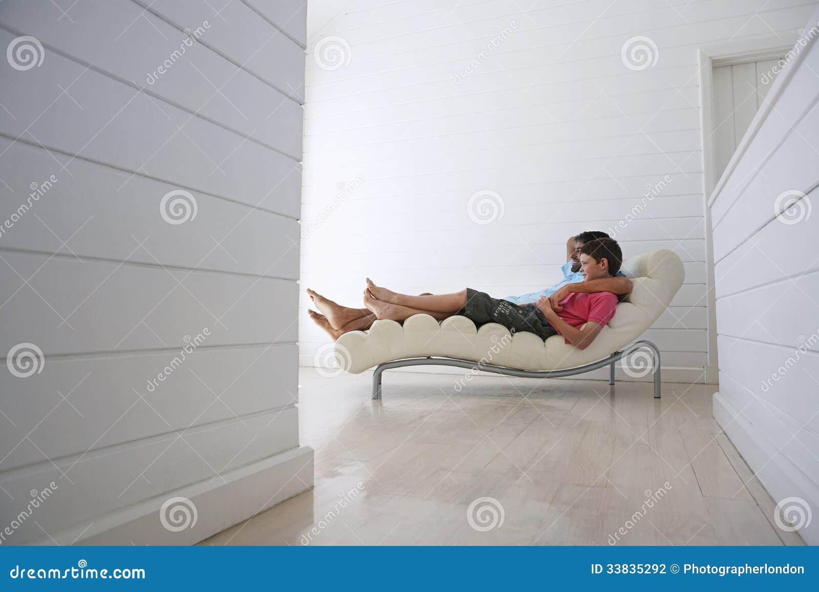 Jongen met de stoel van vaderreclining on lounge stock foto