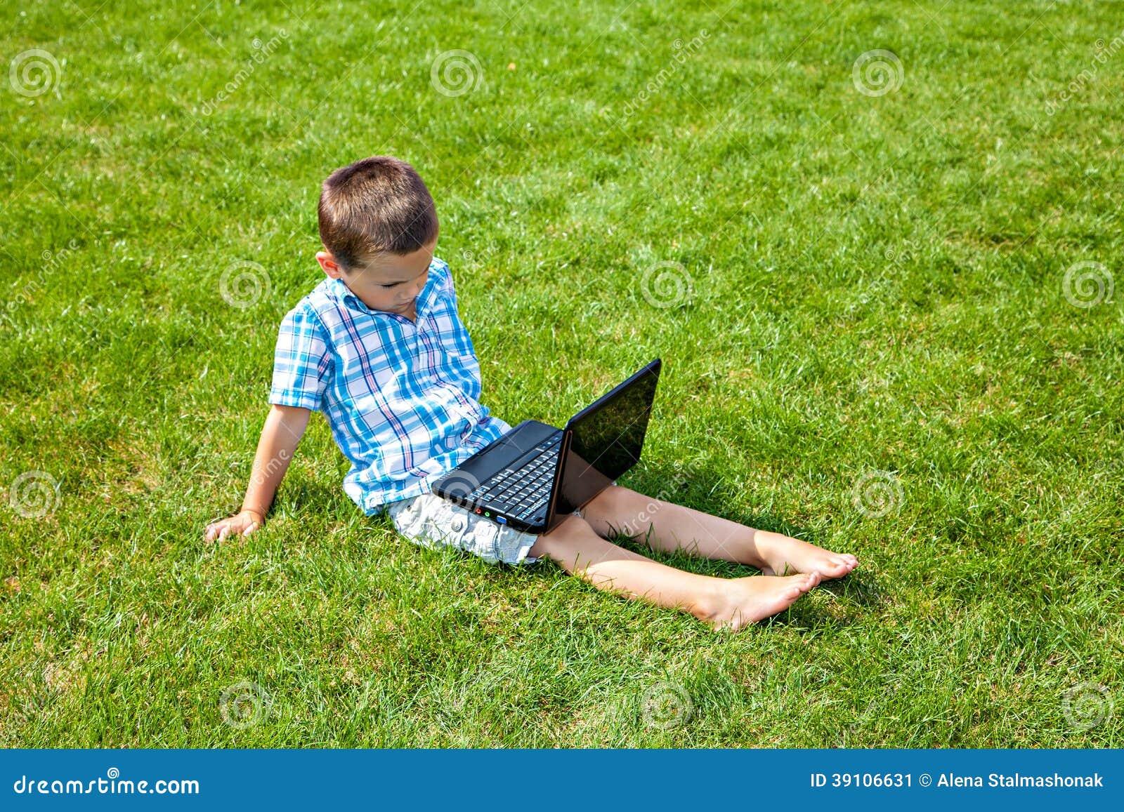 Jongen met laptop zitting op het gras